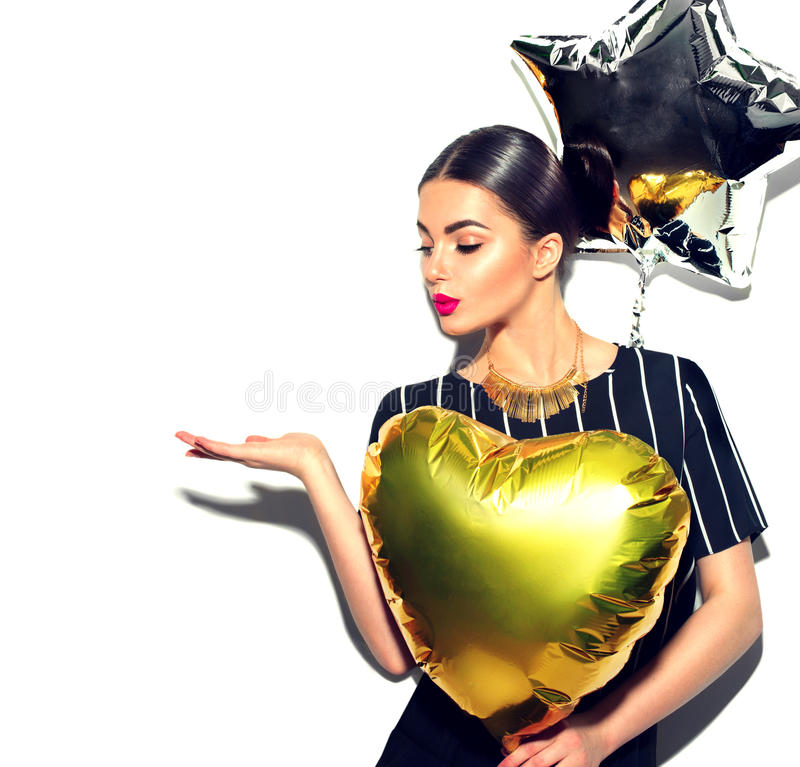 Beauty model girl with colorful balloons showing empty copy space on open hand palm stock image