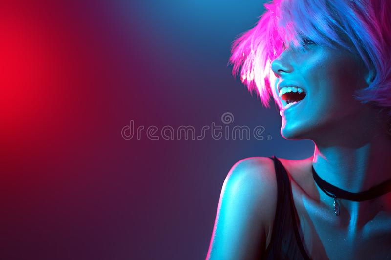 Beauty model girl in colorful bright lights with trendy makeup royalty free stock photography
