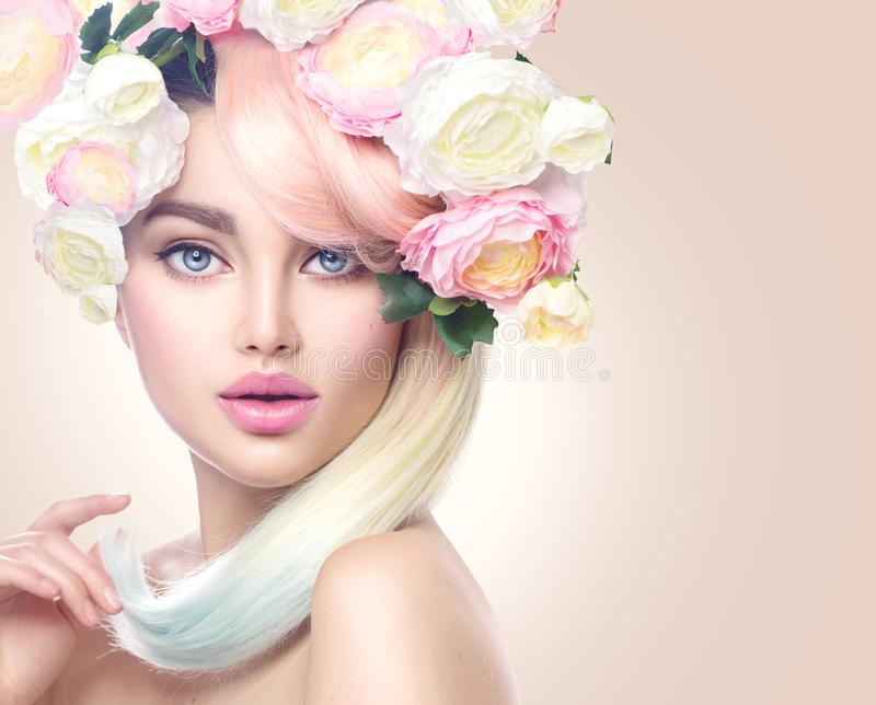Beauty model girl with colorful flowers wreath and colorful hair. Flowers hairstyle. Spring woman portrait. Beauty model girl with colorful flowers wreath and stock image
