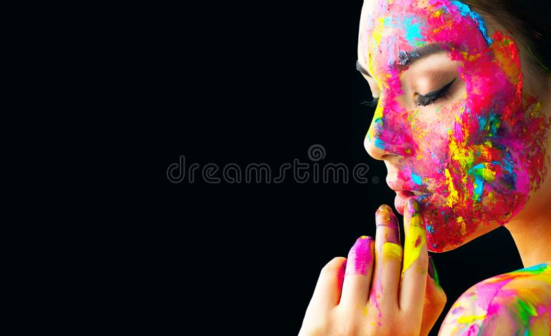 Beauty model girl with colorful paint on her face. Portrait of beautiful woman with flowing liquid paint. Isolated on black stock images