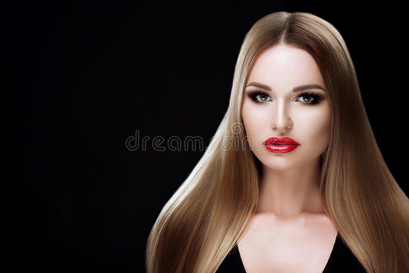 Beauty model girl with healthy blond streaked hair. Beautiful blonde woman with bright makeup, shiny straight hair. Hair stock photography