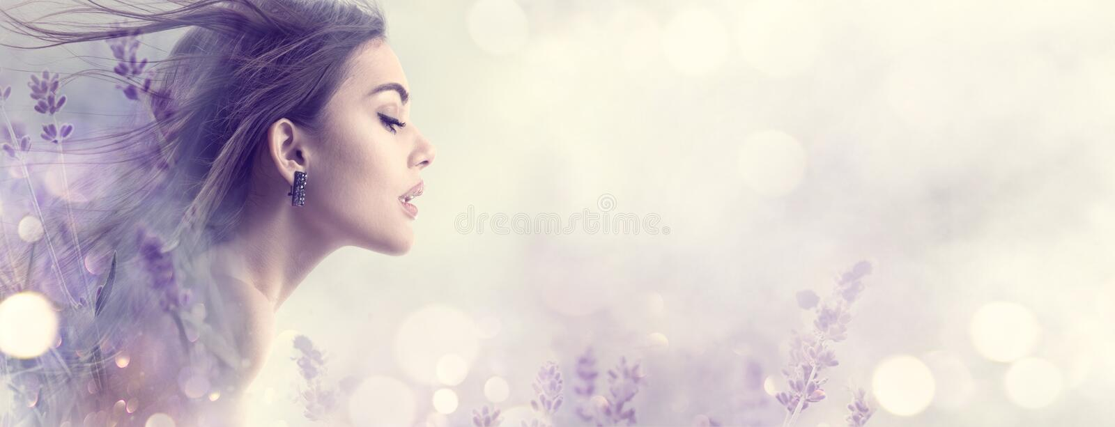 Beauty model girl with lavender flowers. Beautiful young brunette woman with flying long hair profile portrait. Fantasy watercolor stock image