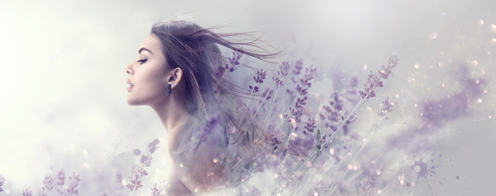 Beauty model girl with lavender flowers. Beautiful young brunette woman with flying long hair profile portrait stock photo