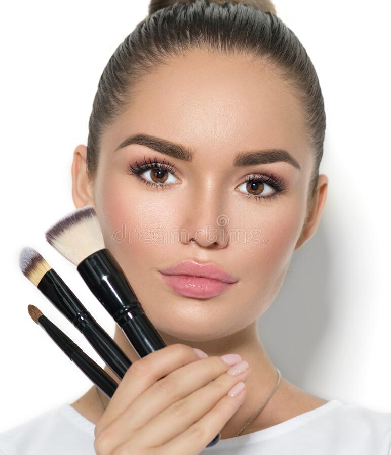 Beauty model girl, makeup artist holding set of make up brushes. Beautiful brunette young woman with perfect skin royalty free stock photography