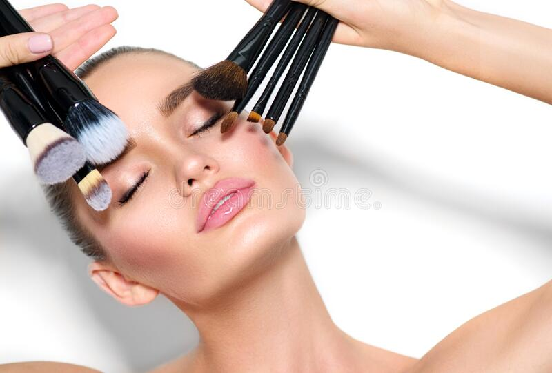 Beauty model girl, makeup artist holding set of make up brushes closeup. Beautiful brunette young woman with perfect skin royalty free stock photos