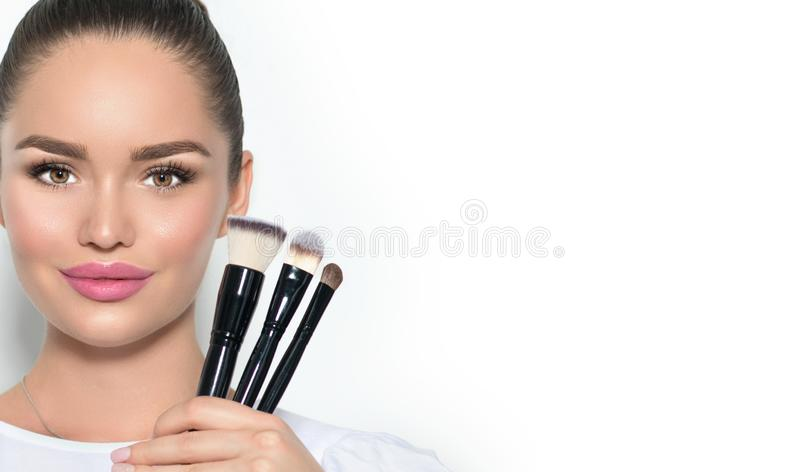Beauty model girl, makeup artist holding set of make up brushes and smiling. Beautiful brunette young woman with perfect skin royalty free stock photos