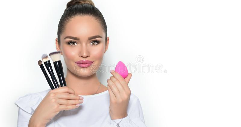Beauty model girl, makeup artist holding set of make up brushes and sponge. Beautiful brunette young woman with perfect skin stock photography