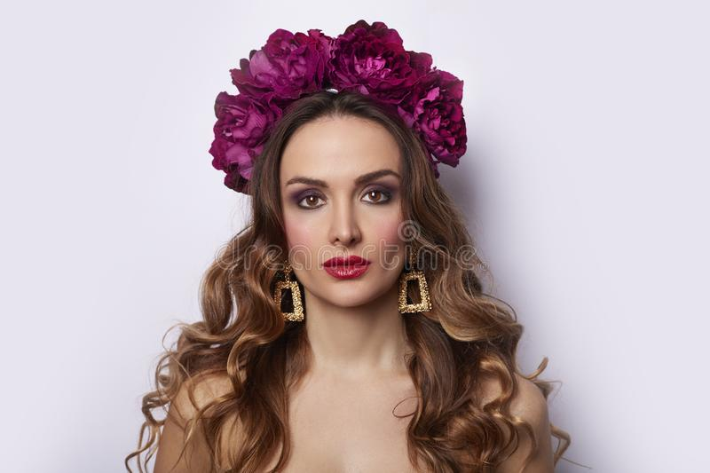 Beauty Model girl with peony flowers wreath. Beautiful brunette young woman perfect holiday trendy make-up red seductive lips royalty free stock photography