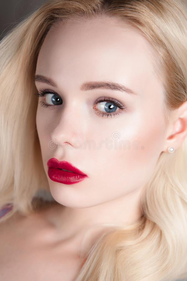 Beauty model girl with perfect make-up red lips and blue eyes looking at camera. Portrait of attractive young woman with blond hai stock image