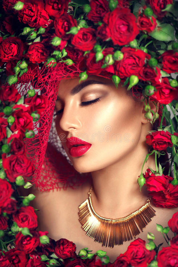 Beauty model girl with red roses flower wreath and fashion makeup. Flowers hairstyle royalty free stock photo
