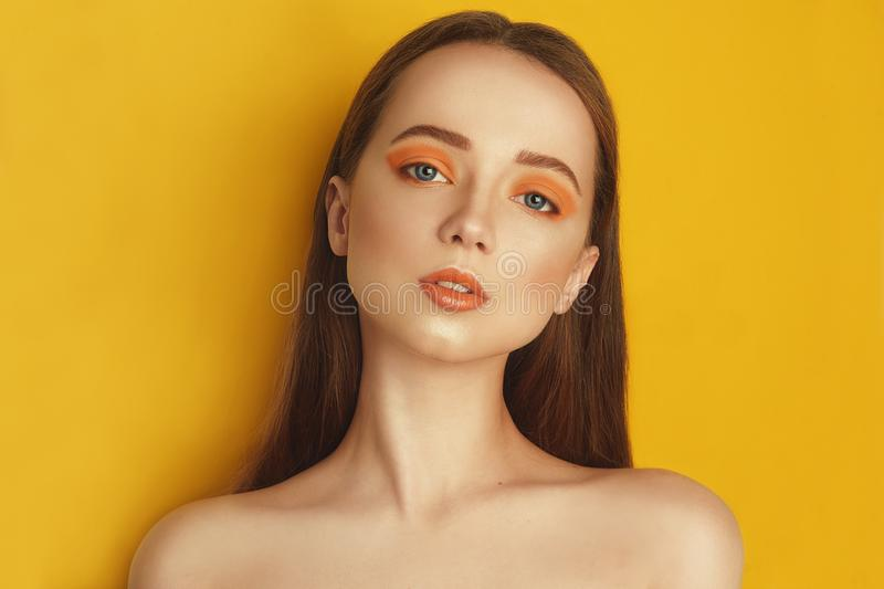 Beauty Model Girl with yellow / orange professional makeup. Orange eye shadow and lipstick  Fashion woman with long, straight hair stock photos