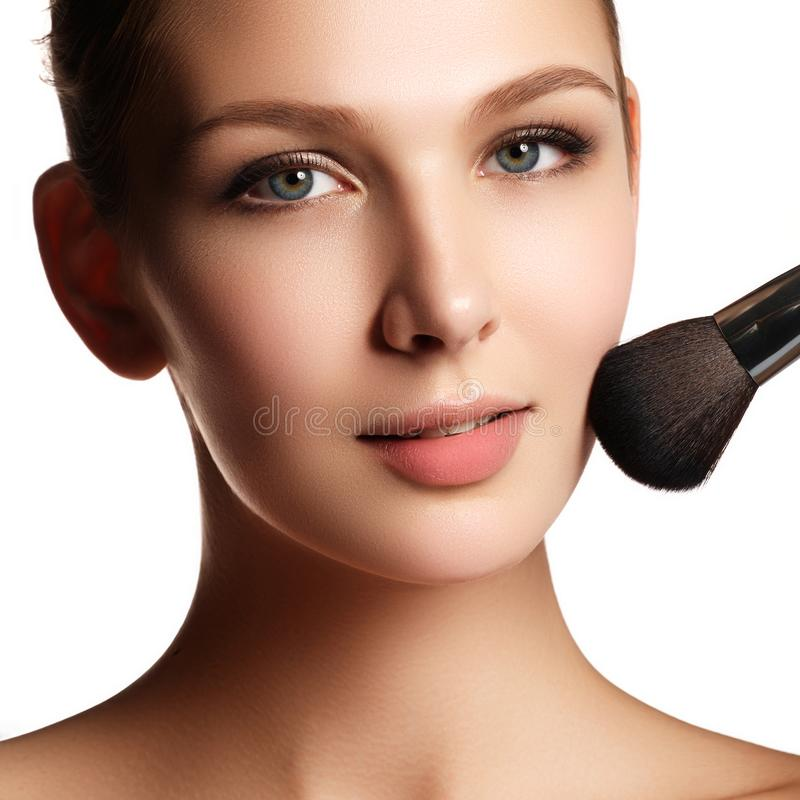 Beauty model with makeup brush. Bright make-up for brunette woma royalty free stock image