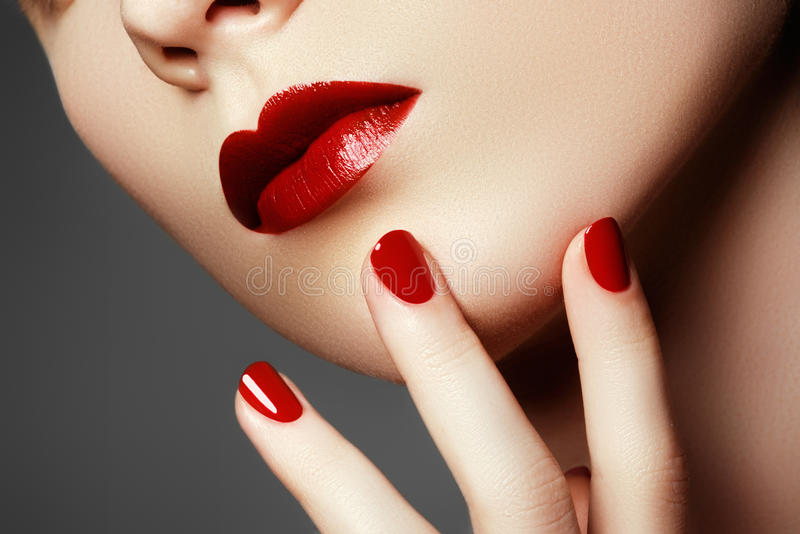 Beauty model. Manicured hand with red nails. Red lips and nails royalty free stock photos