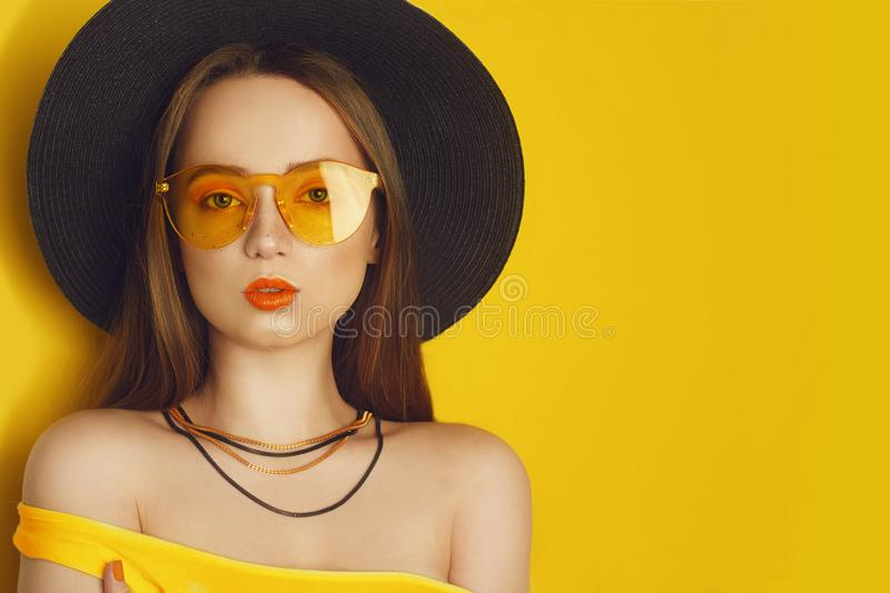 Beauty Model with orange professional look accessories. Fashion woman with long, straight hair. Trend make up. Orange background. royalty free stock photo
