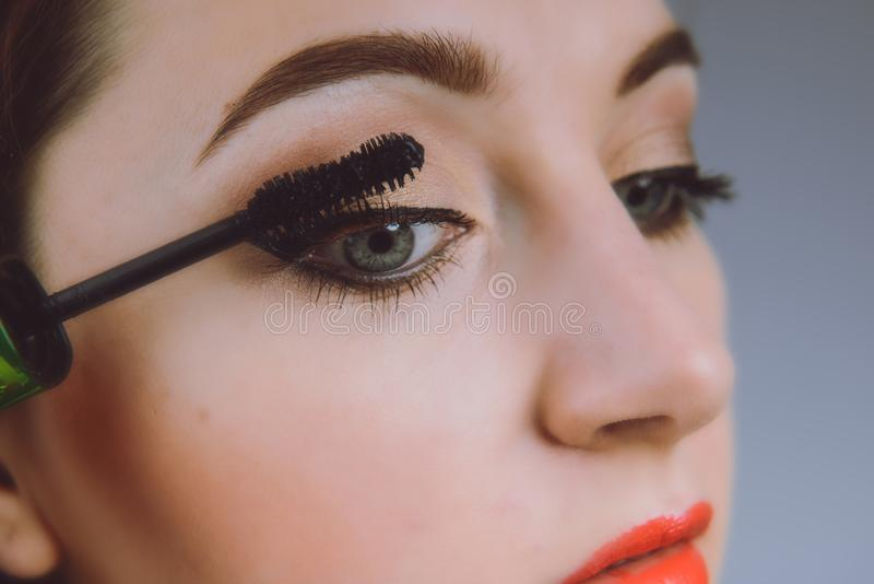 Beauty model teenage girl looking in the mirror and applying mascara make up. Beautiful young woman apply makeup stock photo