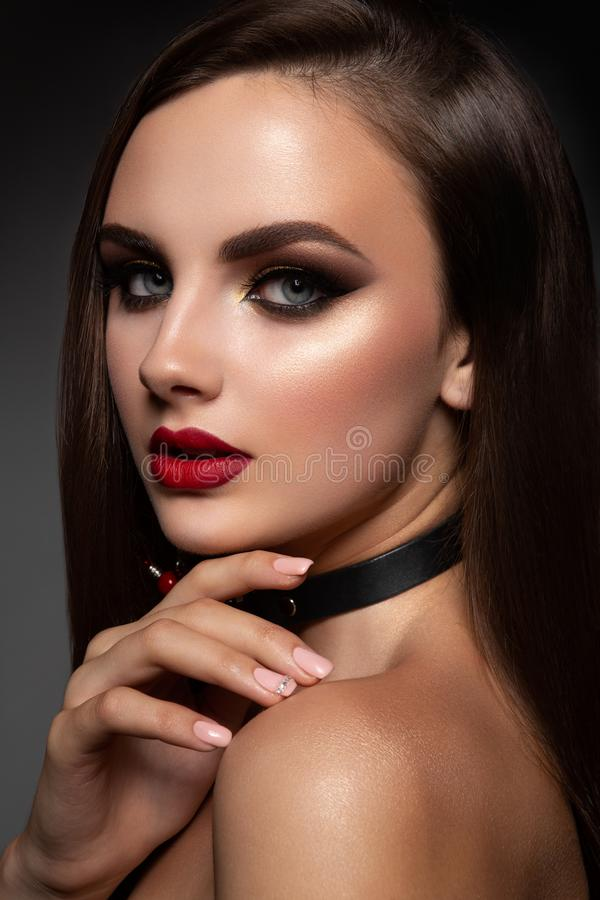 Beauty Model Woman with Long Brown Hair. Healthy Hair and Beautiful Professional Makeup. Red Lips and Smoky Eyes Make up. Gorgeous Glamour Lady Portrait royalty free stock photo
