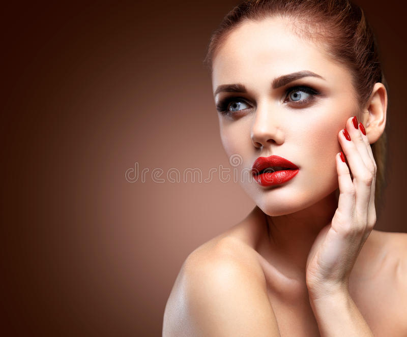 Beauty Model Woman with Long Brown Wavy Hair. Healthy Hair and Beautiful Professional Makeup. Red Lips and Smoky Eyes royalty free stock image