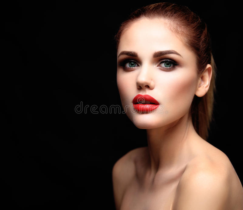Beauty Model Woman with Long Brown Wavy Hair. Healthy Hair and Beautiful Professional Makeup. Red Lips and Smoky Eyes stock photography