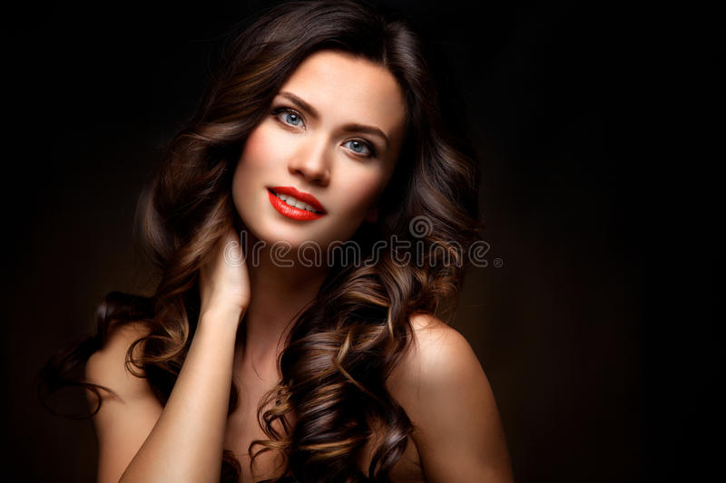 Beauty Model Woman with Long Brown Wavy Hair. Healthy Hair and Beautiful Professional Makeup. Red Lips and Smoky Eyes royalty free stock photos