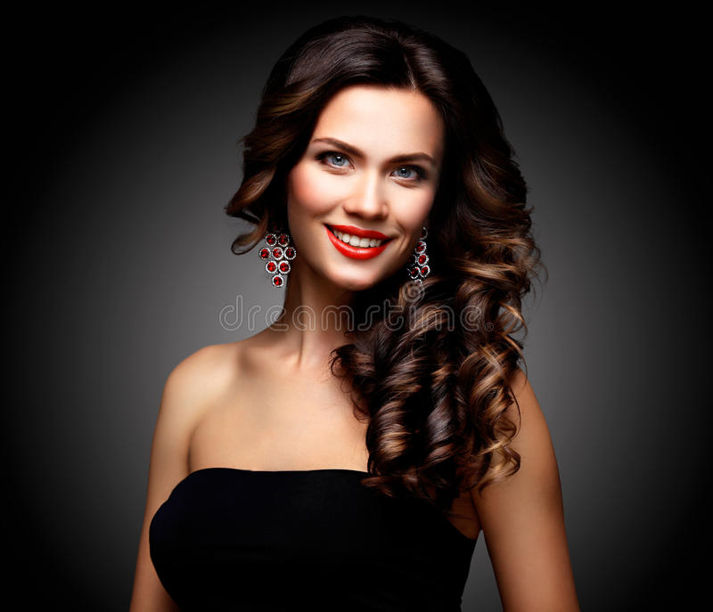 Beauty Model Woman with Long Brown Wavy Hair. Healthy Hair and Beautiful Professional Makeup. Red Lips and Smoky Eyes stock photo