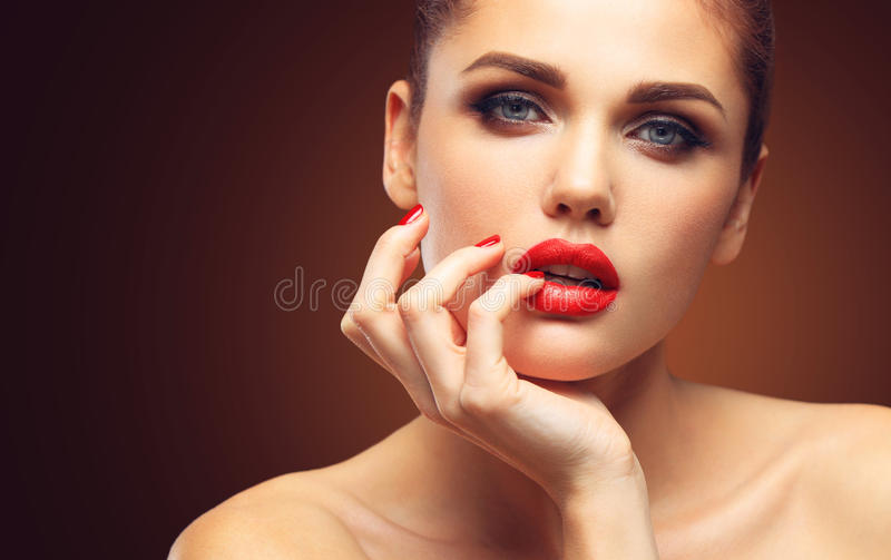 Beauty Model Woman with Long Brown Wavy Hair. Healthy Hair and Beautiful Professional Makeup. Red Lips and Smoky Eyes stock images