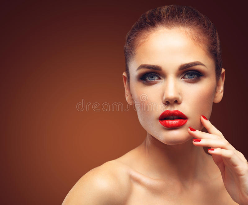 Beauty Model Woman with Long Brown Wavy Hair. Healthy Hair and Beautiful Professional Makeup. Red Lips and Smoky Eyes stock photos