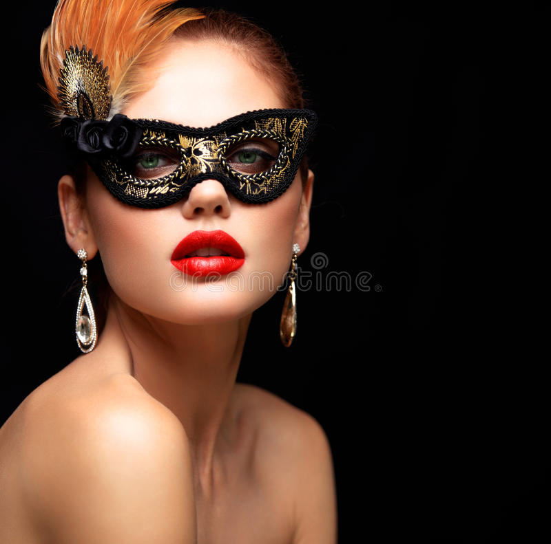 Beauty model woman wearing venetian masquerade carnival mask at party isolated on black background. Christmas and New stock photos