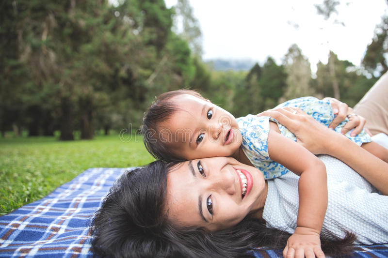Beauty Mum and her Child playing in Park together stock images