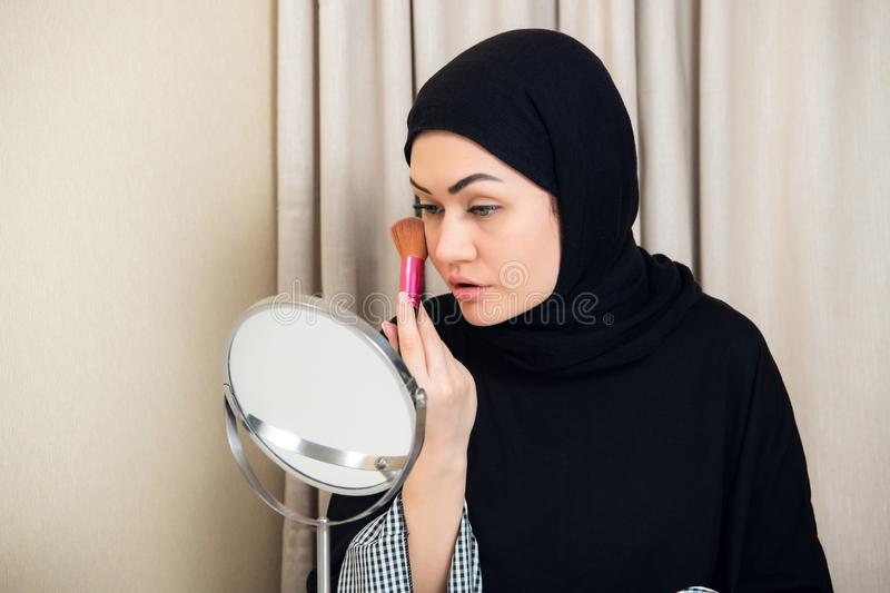 Beauty muslim woman with hijab applying makeup. Beautiful girl looking in the mirror and applying cosmetic. Girl gets royalty free stock photos