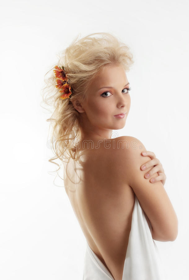 Beauty naked woman with flower in blond hair royalty free stock images