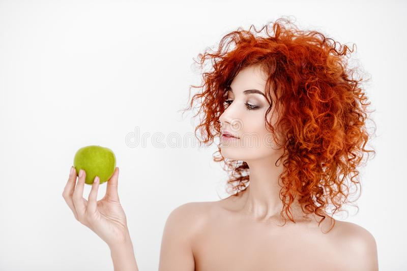Natural cosmetics concept. Beauty, natural cosmetics and hair concept. Beautiful young woman with bright red curly hair and healthy shiny skin holding a green royalty free stock photography