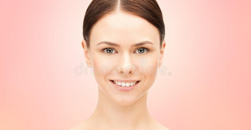 Face of beautiful woman over pink background stock images