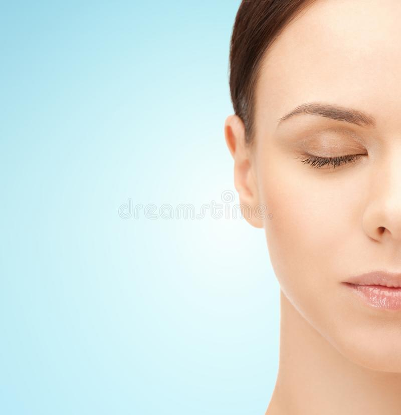 Half face of young woman over blue background stock photography