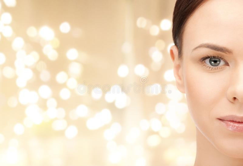 Half face of young woman over lights background royalty free stock photography