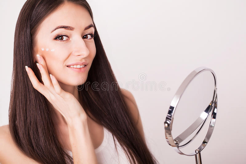 Beauty, people, cosmetics, skincare and health concept - happy smiling young woman applying cream to her face royalty free stock photo