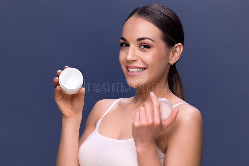 beauty, people, skincare and cosmetics concept - woman with moisturizing cream on hand and facial. royalty free stock images