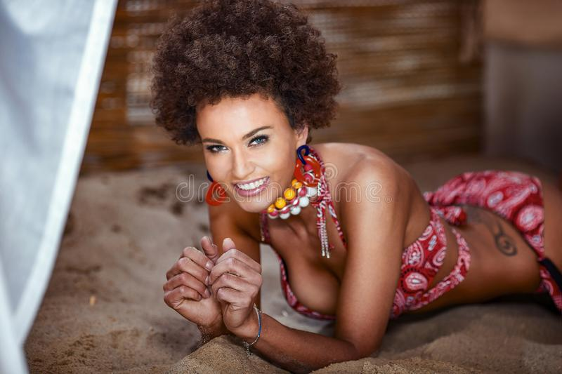 Beauty photo of natural girl with afro lying on sand stock photography
