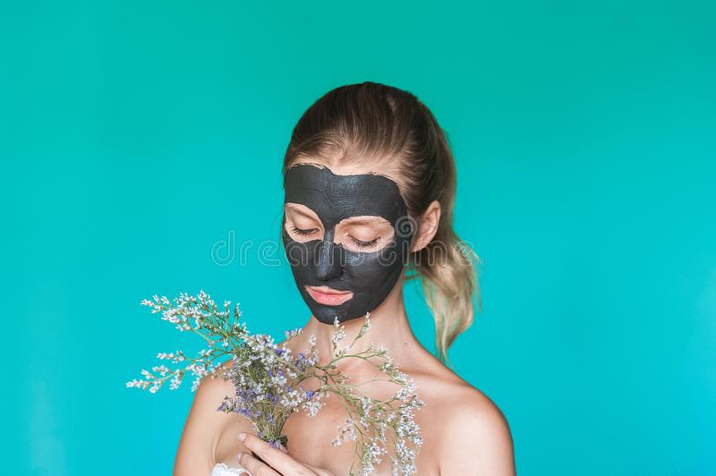 Beauty photo of a woman with a black mask on her face is holding dry wild flowers in the background against a blue wall. Beauty photo of a woman with a black royalty free stock photo