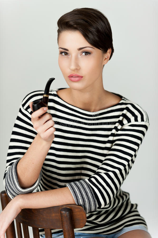 Beauty with pipe. Attractive young short hair woman in striped clothing smoking pipe and looking t camera royalty free stock images