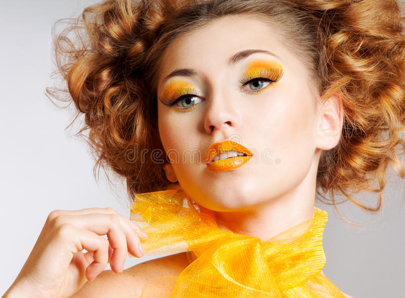 Beauty portrait. Beautiful woman with bright creative yellow makeup and curly hairstyle royalty free stock image