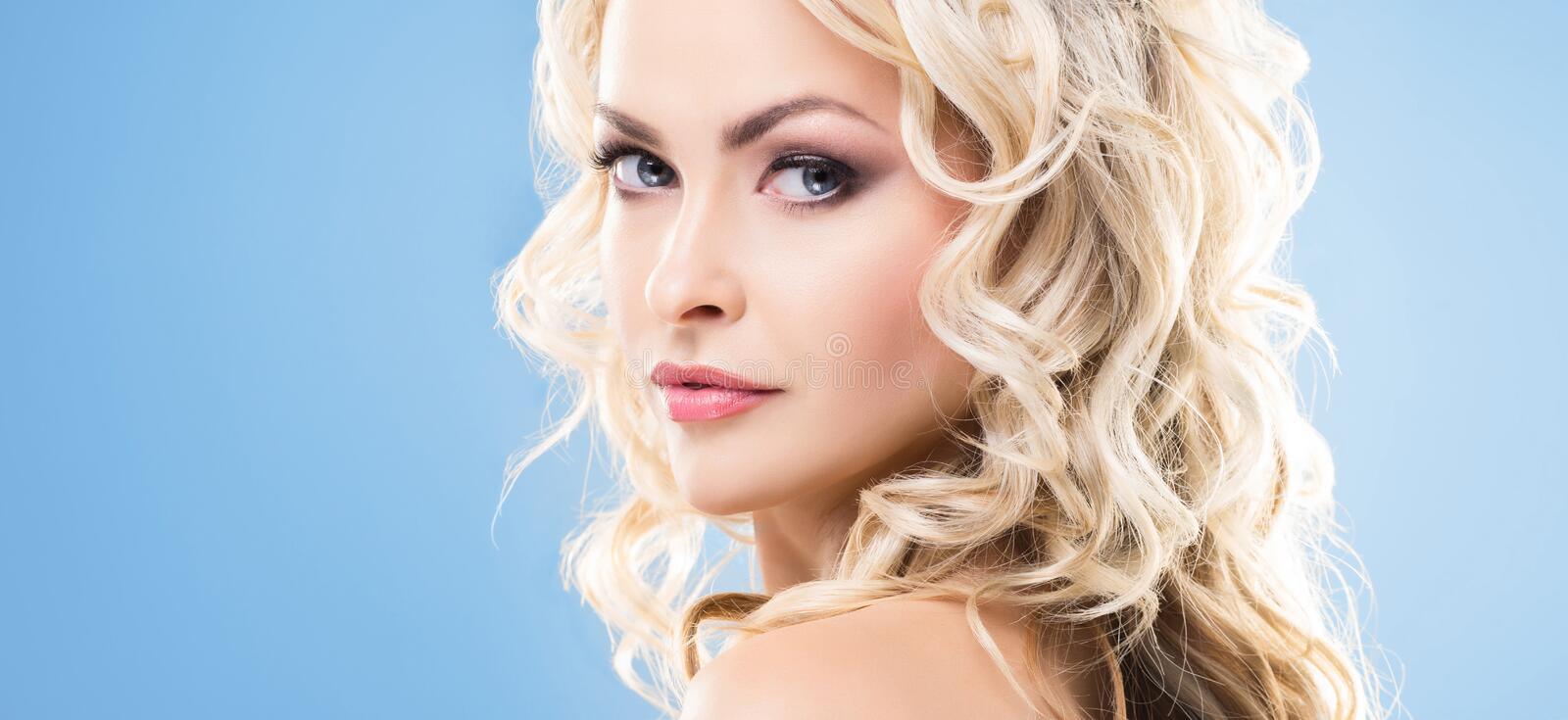 Beauty portrait of attractive blond woman with curly hair and a beautiful hairstyle. Makeup and cosmetics, face lifting royalty free stock photo