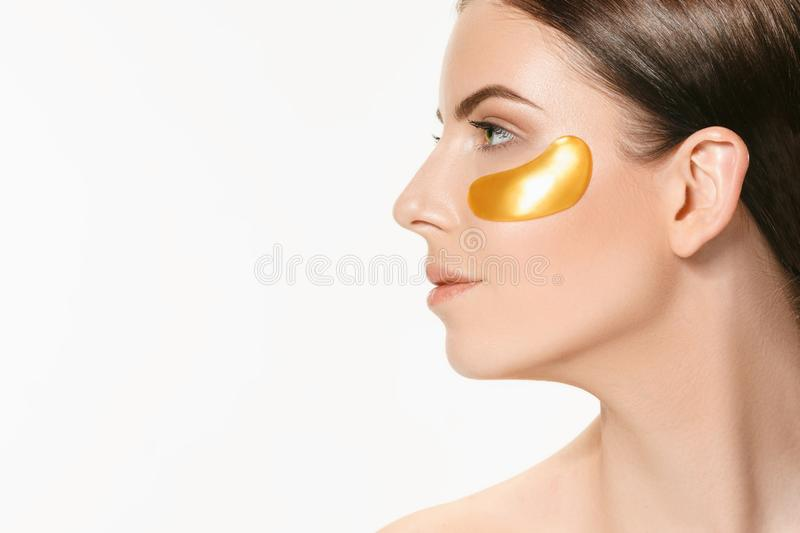 Beauty portrait of an attractive girl with a gold patch under the eye. royalty free stock photography