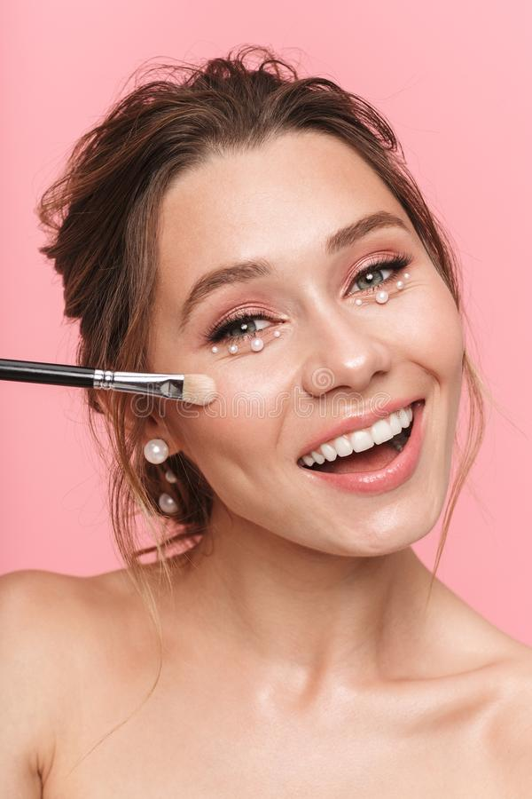 Beauty portrait of an attractive young topless woman. Applying makeup with a brush over pink background, wearing white pearls royalty free stock images