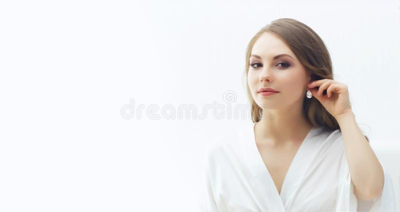 Beauty portrait of attractive and young woman trying pearl earrings. royalty free stock photography