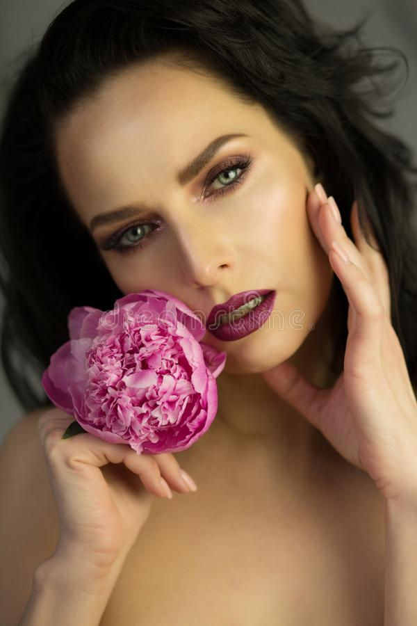 Beauty portrait of beautiful brunette lady with pink peony flower in hand. Spring blossom concept. Studio shot royalty free stock images