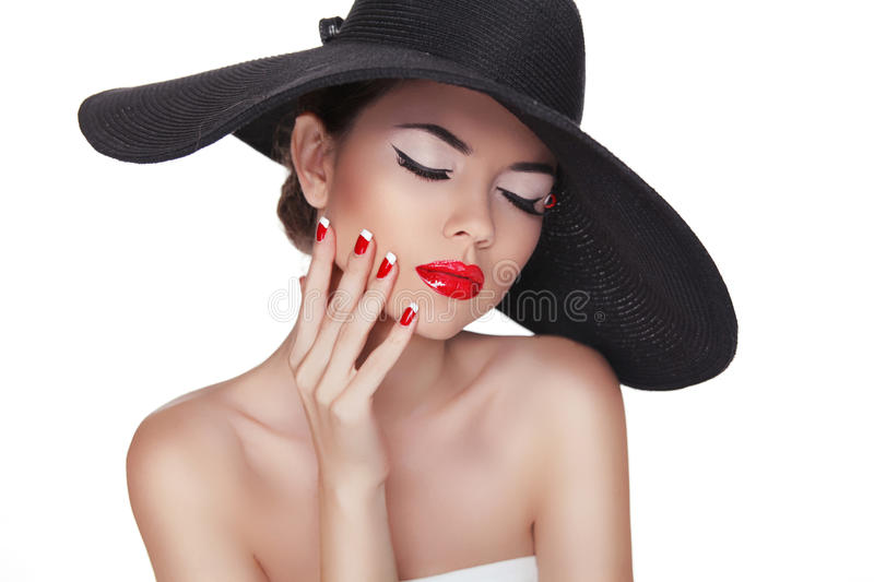 Beauty portrait of beautiful fashion woman with black hat, professional makeup and red manicure isolated on white background royalty free stock photography