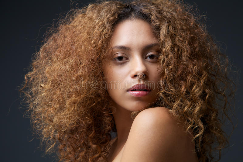 Beauty portrait of a beautiful female fashion model with curly hair royalty free stock photo