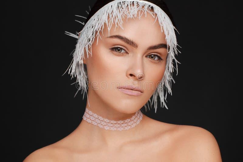 Beauty portrait of a beautiful woman using white lace ribbon. Black background royalty free stock photo