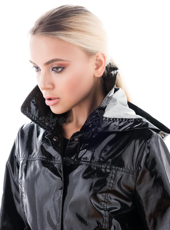Beauty portrait of beautiful young woman in a black glossy coat royalty free stock photos