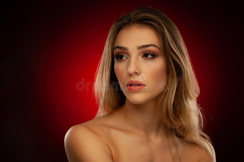 Beauty portrait of a beautiful young woman with brown long hair over dark red background royalty free stock photo